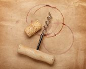 Cork and corkscrew with red wine stains on brown paper background