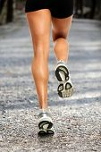 stock photo of dirt road  - Legs of female runner on dirt gravel road - JPG