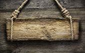 Wooden sign hanging on a rope on wooden background
