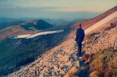 Spring landscape with man tourist on a mountain trail. Carpathians, Ukraine, Europe. Filtered image: vintage, grunge and texture effects