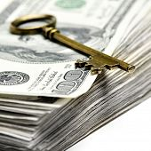 pic of skeleton key  - Old key laying on top of stack of cash money - JPG