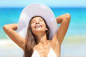 Beach woman enjoying sun tanning on travel smiling under blue sky. Cheerful beautiful bikini girl su