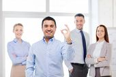 office, business, and teamwork concept - friendly young smiling businessman with team on back showing ok-sign