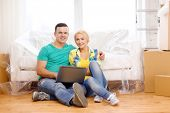 moving, home, technology and couple concept - smiling couple with laptop sitting on floor in new hou