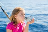 Blond kid girl fishing tuna little tunny kissing fish for release due tiny size