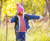 Hiking kid girl with backpack pointing finger in autum poplar trees forest