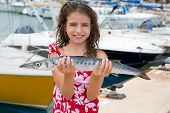 Happy kid fisherwoman with barracuda fish catch in Mediterranean marina