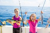 stock photo of boat  - Happy tuna fisherwomen kid girls on boat with fishes trolling catch with dorado Mahi - JPG