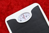 Bathroom scale on red bath mat