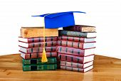 Graduation Mortarboard On Top Of Stack Of Books On White Isolated  Background
