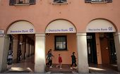 BOLOGNA, ITALY - APRIL 19, 2014: A group of pedestrians walk past a branch office of Deutsche Bank i