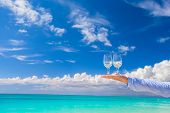 Two glasses on hand on blue sky background