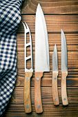 stock photo of food preparation tools equipment  - set of kitchen knives on old wooden table - JPG
