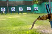 picture of archery  - Standard colorful target for archery. Sporting a bow and arrows in the foreground