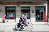 BOLOGNA, ITALY - APRIL 19, 2014: Pedestrians go past a  Unicredit Banca di Roma S.p.A bank office in
