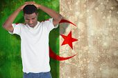 Disappointed football fan looking down against algeria flag in grunge effect