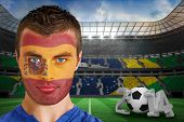 Composite image of serious young spain fan with facepaint against large football stadium