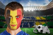 Composite image of serious young belgium fan with face paint against large football stadium with bra