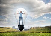 Angry woman in light bulb against cityscape in distance in bright landscape