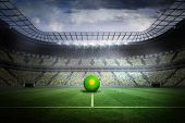 Bright green and yellow football in a large football stadium with fans in yellow