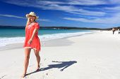 stock photo of floaties  - Happy woman walking along a beautiful white sandy beach in sunny Australia - JPG