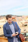 Young urban businessman professional using smartphone using app texting sms message on smart phone w