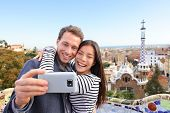 Travel couple happy talking selfie self-portrait with smartphone in Park Guell, Barcelona, Spain. Be