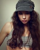Sexy Hiphop Woman In Cap With Long Curly Hair. Vintage Portrait