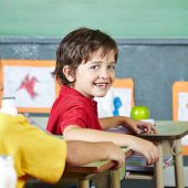 Happy abecedarian child sitting smiling in elementary school classroom