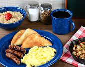 A country style scrambled egg breakfast on a rustic wooden restaurant table. Eggs, sausage links, to