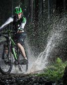 Mountain biker speeding through forest stream, water splash in freeze motion.