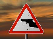 Triangle sign with handgun and bullets holes, sunset
