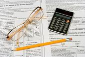 Glasses, pencil and calculator on business background