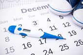 stock photo of intercourse  - Electronic thermometer in fertility concept on calendar - JPG
