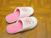 Childlike slippers on parquet, bear with heart