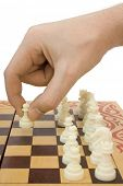 Pawn in hand and chessboard, isolated on white background