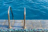 Metal staircase to water in swimming pool