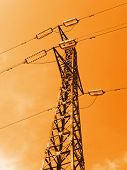 Electricity pylon on sky background, orange toning