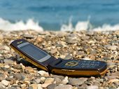 Open mobile phone on beach, sea on background
