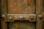 stock photo of southwest  - A wooden door panel in the southwest with metal trim and patterns carved into the edges - JPG