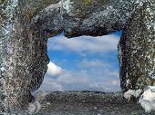 Window in stone wall, cloudy sky