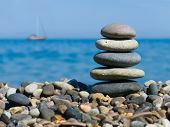 Stack of stones on beach and yacht in sea