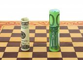 Money ( dollar and euro ) on chess board, isolated on white background