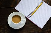 Notebook Pencil And Cup Of Coffee In Wood Table