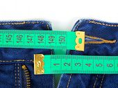 Jeans and measuring tape - sliming, isolated on white background