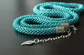 Necklace From Beads Of Color Aquamarine Against A Dark Background