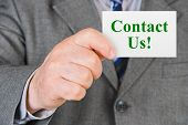 Card Contact us in hand - business background
