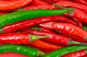 Heap of green and red hot chili pepper - food background