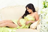 Beautiful Motherhood. Pregnant In  Tender Light Green Dress On A Sofa With Lilies
