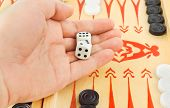 Hand with dices and backgammon game